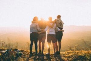 Vier Menschen stehen Arm in Arm im Sonnenuntergang