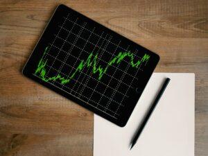 Tablet mit Graph, Zettel und Stift auf einem Tisch
